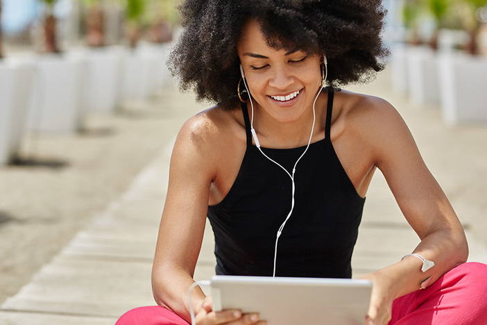 Pretty afro american woman listening audiobook on tablet smiling