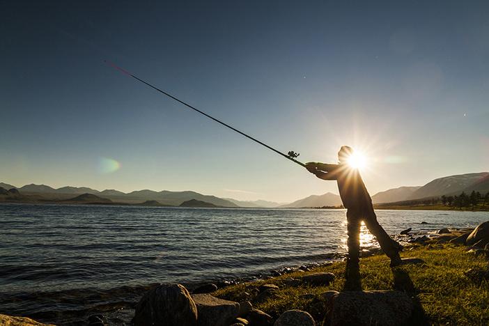 Silhouette of a fisherman at sunset. Fishing on mountain lake