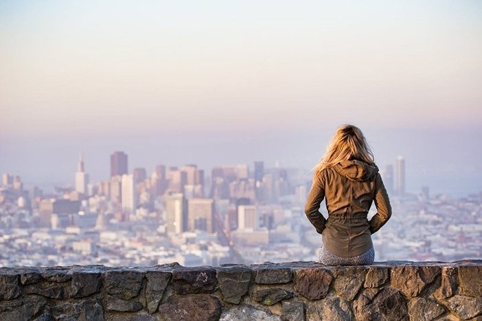 blond woman sitting on ledge looking out of city skyline