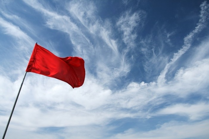 blue sky background with some clouds and red flag in foreground waving in wind