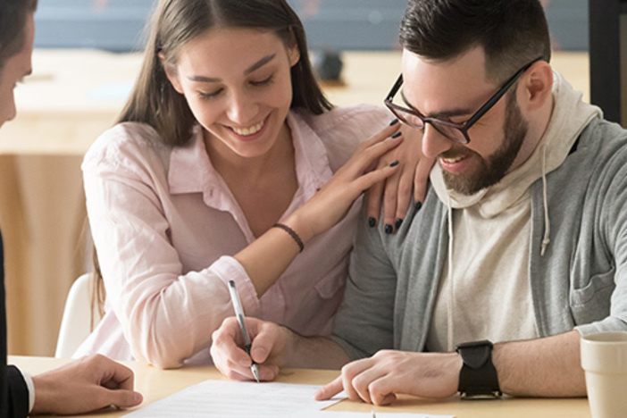 couple signing real estate closing documents