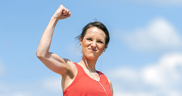 woman with victorious fist in air signifying accomplishment