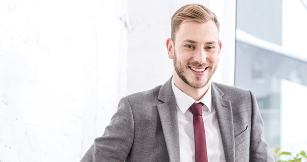 smiling businessman drinking coffee in kitchen and looking at camera