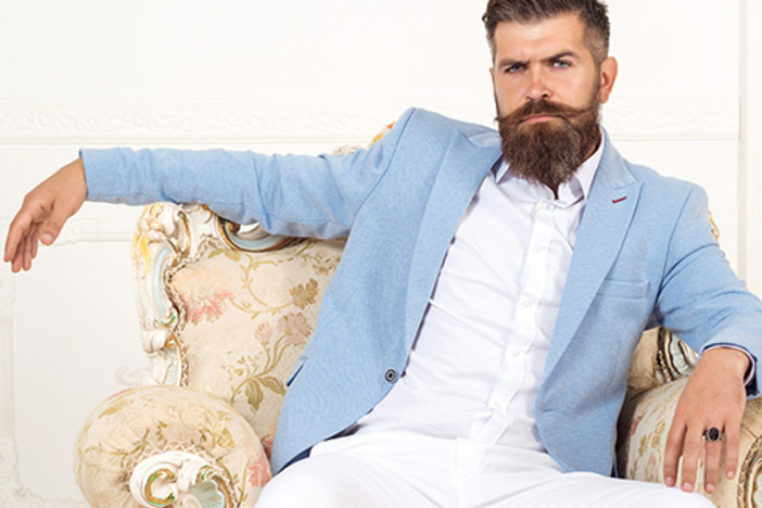 Successful young bearded elegant businessman in suit with perfect hairstyle indoors, relaxing, sits on arm chair, looks harsh and virile. Rich man wearing blue jacket and white pants. Fashion concept