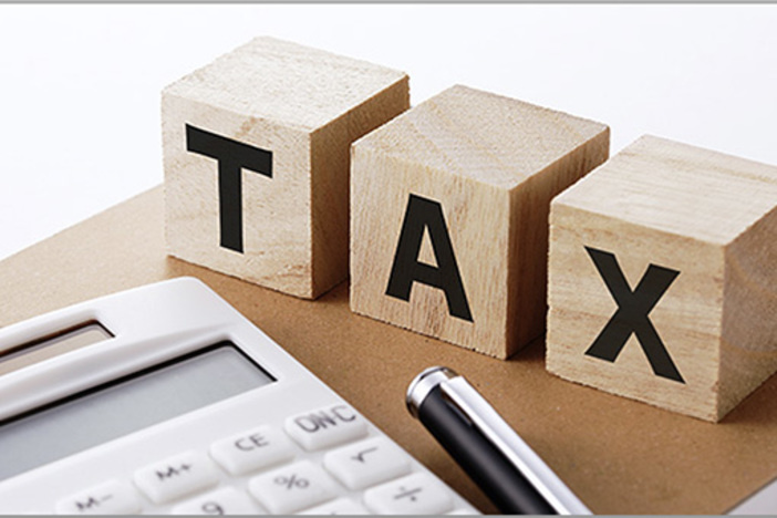 letters taxes on wooden blocks with calculator and pen