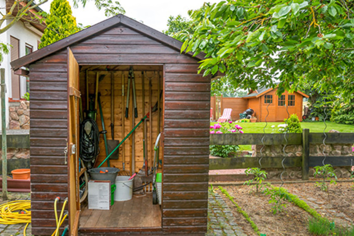 storage shed with door ajar and landscaping tools inside set in a backyard with green grass and pristine landscaping