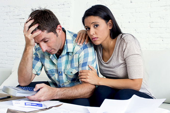 young sad couple at home living room couch calculating monthly expenses worried