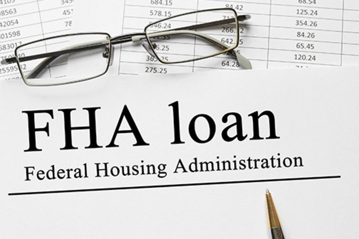 Paper titled FHA loan staked on top of spreadsheets on a table with a pen and glasses
