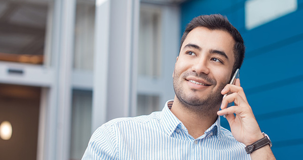 Happy young man on phone, indoors - inside. Close up of businessman talking on mobile phone - smartphone. Comunicative friendly hispanic man