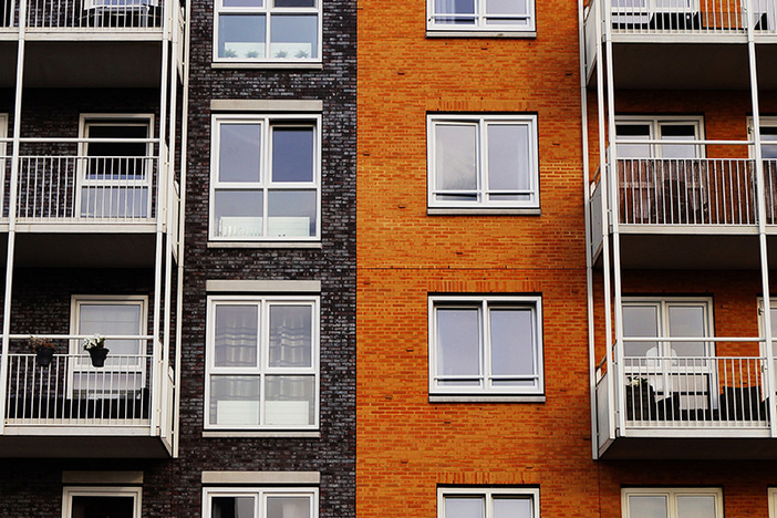 exterior of large apartment building with black and orange brick and white trim