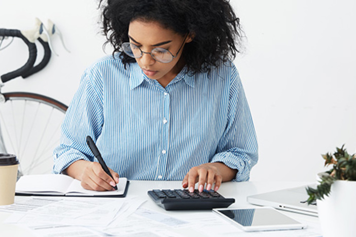 businesswoman doing paperwork at office desk, working through finances, using calculator and making notes in her notebook with pen