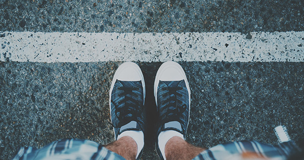 View of feet of guy in white socks and sneakers standing near grunge white line on asphalted road, ready to pass