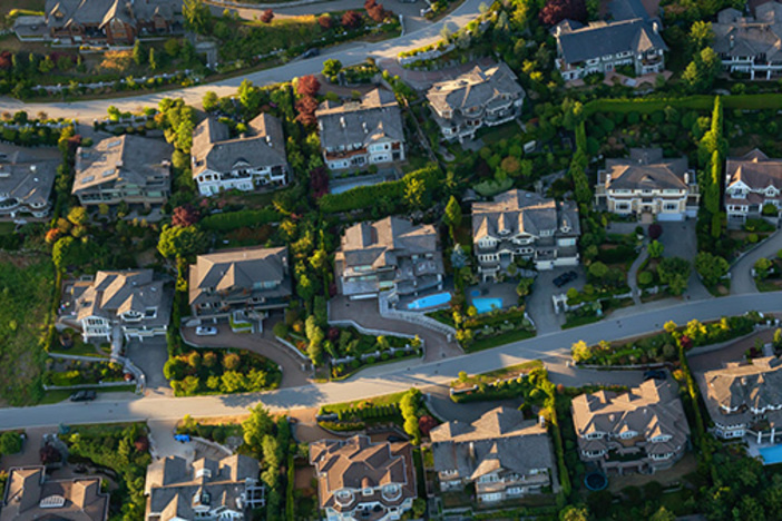 Aerial view of the big luxury homes on the hill during a vibrant sunny summer day.