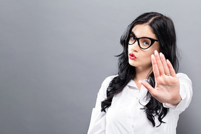woman with hand extended out gesturing stop or rejection
