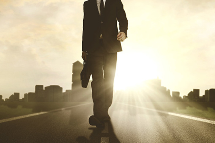 Low angle view of a young male manager carrying a briefcase while walking on the road with skyscraper background