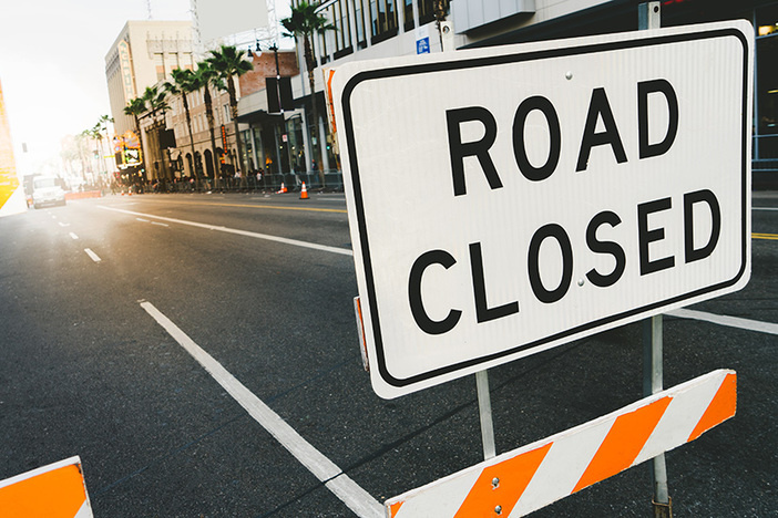 Road closed sign and traffice cone in the street. Traffic control sign road closed in the city. Road closed sign on Hollywood Boulevard.