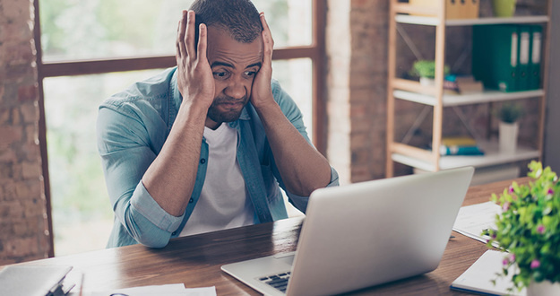 Frustrated young african entrepreneur with sad grimace in front of his laptop in office, noticed a big mistake he did, holding his face with arms palms, wearing jeans casual smart