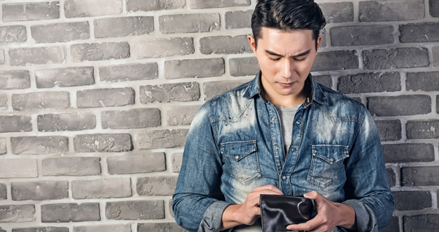man against gray brick background looking down into empty wallet
