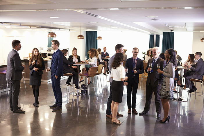 Business people networking and having cocktails at meetup in conference room setting