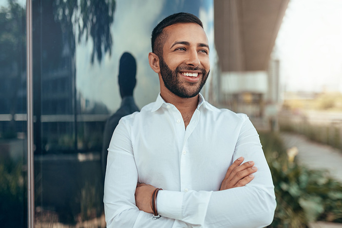 Portrait of a young confident smiling indian man with his arms crossed looking into the distance