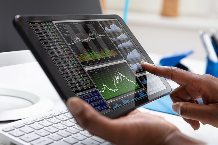 Close-up Of A Businessperson Pointing On Stock Chart Over The Tablet Screen