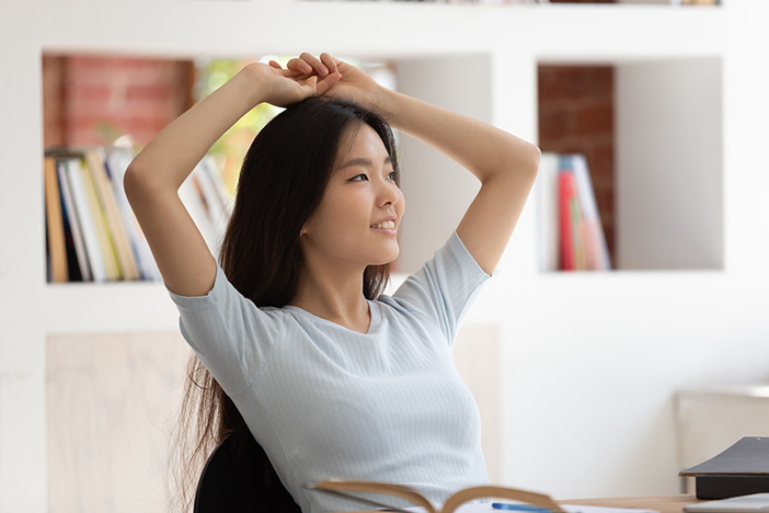 Calm asian student girl sitting at desk resting after studying