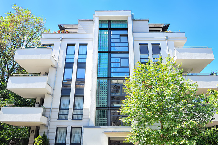 medium size apartment building with light gray cement exterior and lots of windows against a vibrant blue sky
