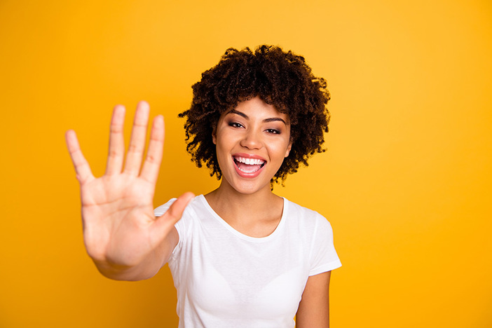 Close up photo beautiful amazed she her dark skin lady glad arms hands five fingers raised show countable uncountable things lesson wearing casual white t-shirt isolated yellow bright background.