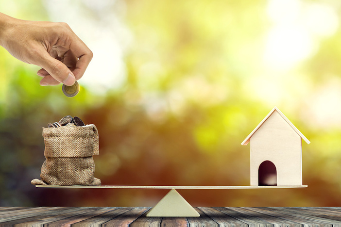 Real estate investment, home loan, reverse mortgage, savings to buy home concepts. House wood model, Hand putting coin into a bags on wood balance scale. depicts a funding for real estate investment.