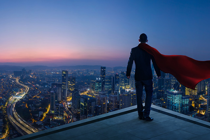 Businessman in suit and hero cape stand at rooftop looking great cityscape view at night
