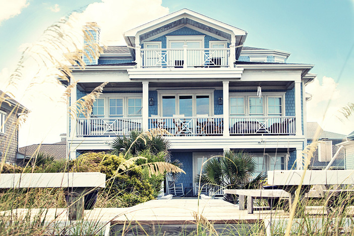blue vacation beach rental property with blue siding and white trim and two upper floor balconies on beach