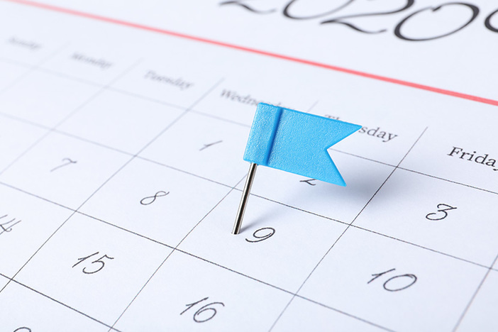 Calendar page marked with drawing pin, closeup