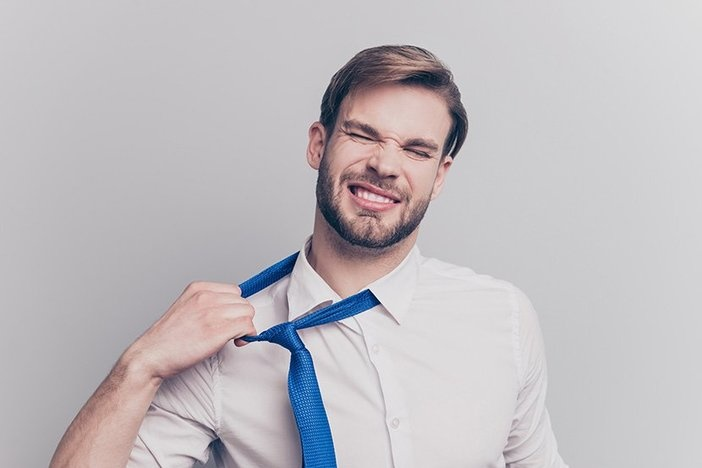 Close up portrait of exhausted frustrated stressed handsome sad unhappy upset entrepreneur trying to take off uncomfortable blue tie formal wear isolated on gray background copy-space