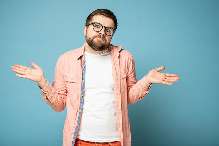 Bearded man with glasses, with an innocent look, shrugs, spreads his arms to the sides and looks into the camera with big eyes. Isolated on a blue background.