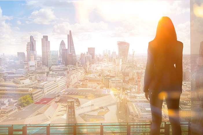 Young woman looking over the City of London at sun set.