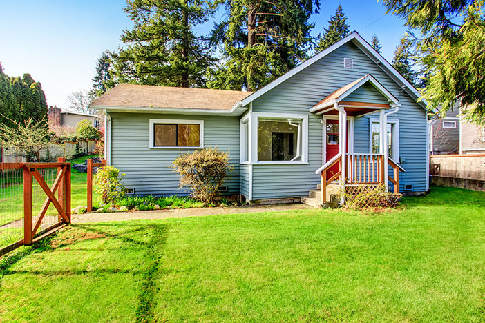 Small grey house with wooden deck. Front yard with flower bed and lawn.