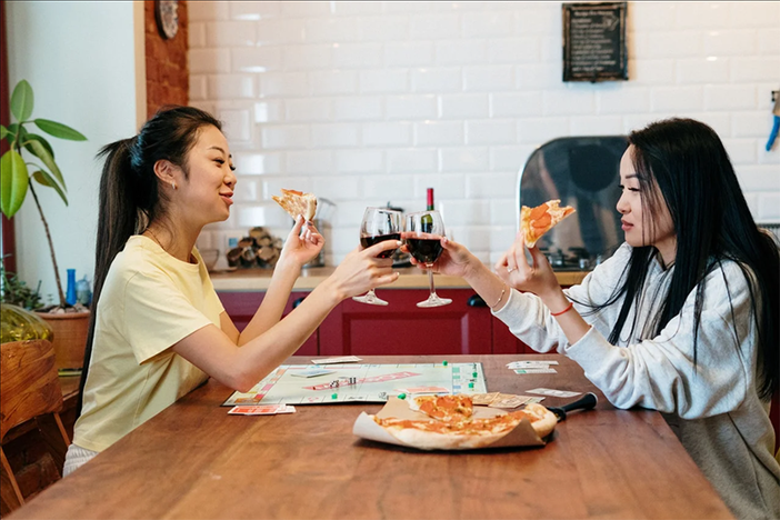two women at kitchen table eating pizza and playing monopoly