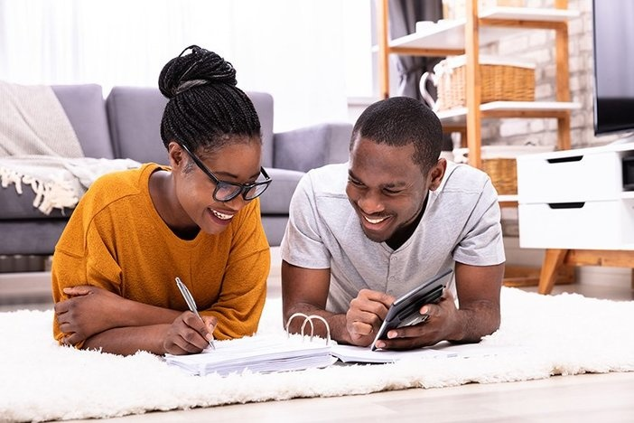 Young Couple Lying On Carpet Invoice With Calculator
