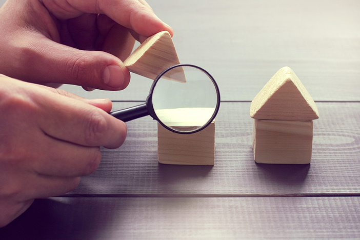 viewing in a magnifying glass the design of a house layout / inspection of construction objects