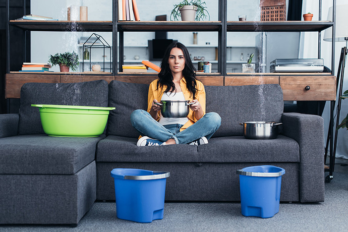 Beautiful woman with pots and buckets dealing with water damage in living room
