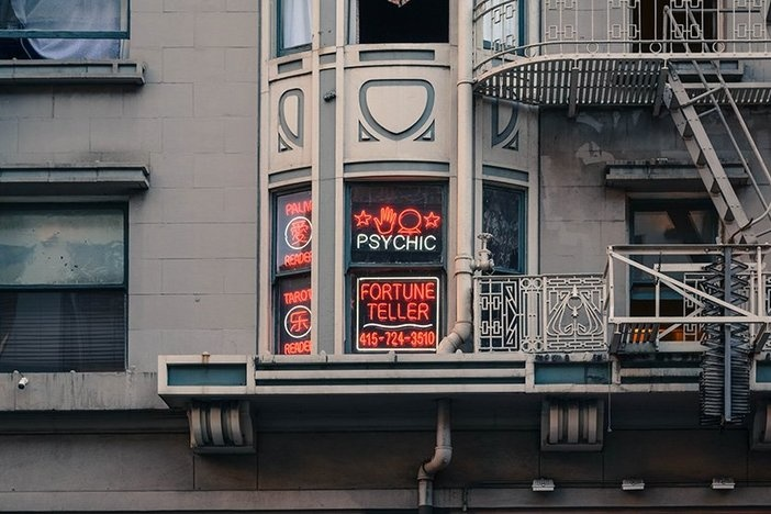 tan mixed use building with neon sign advertising psychic and fortune telling