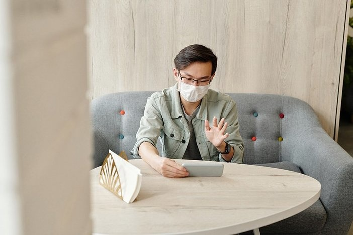 man seated at table wearing mask looking at phone in hand and waving to someone on video call