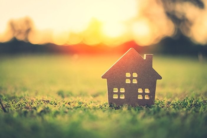 Small model home on green grass with sunlight abstract background. Vintage tone filter effect color style.