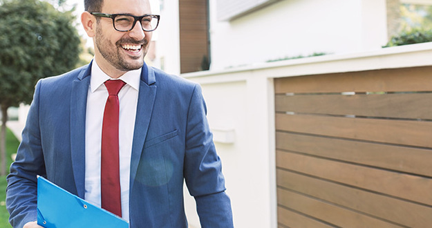 smiling brown-haired man with glasses and shadow of a beard evaluates exterior of a residential property while wearing suit and carrying a folder