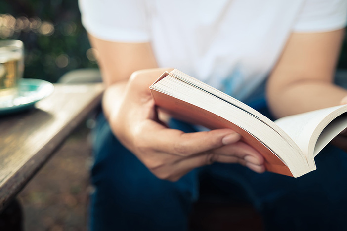 closeup of man in white shirt and blue jeans sitting and reading a paperback book