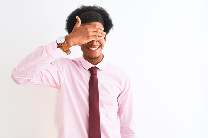 Young african american businessman wearing tie standing over isolated white background smiling and laughing with hand on face covering eyes for surprise. Blind concept.