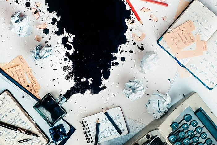 Writer workplace with spilled ink, stationery and a typewriter. Crumpled paper balls with pencils on a white wooden background, creative writing concept.