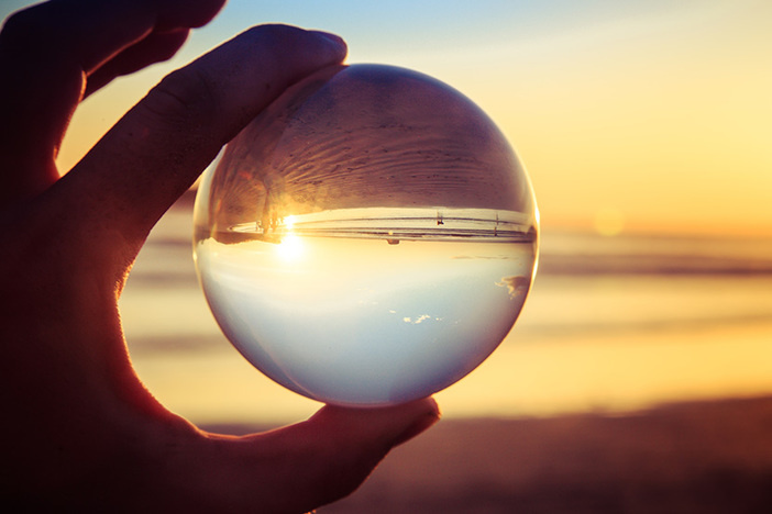 Landscape concept with crystal ball or esphere in hand during sunset on beach