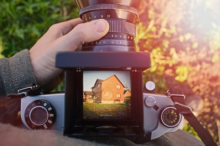 man photographer is making arhitecture photography with old film camera in spring, home and building concept. top view.