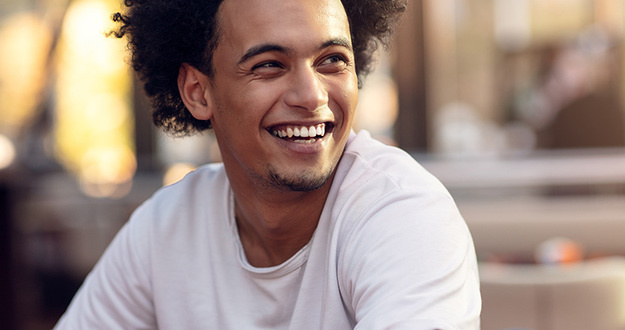 Close up portrait of handsome cheerful african man smiling looking at camera